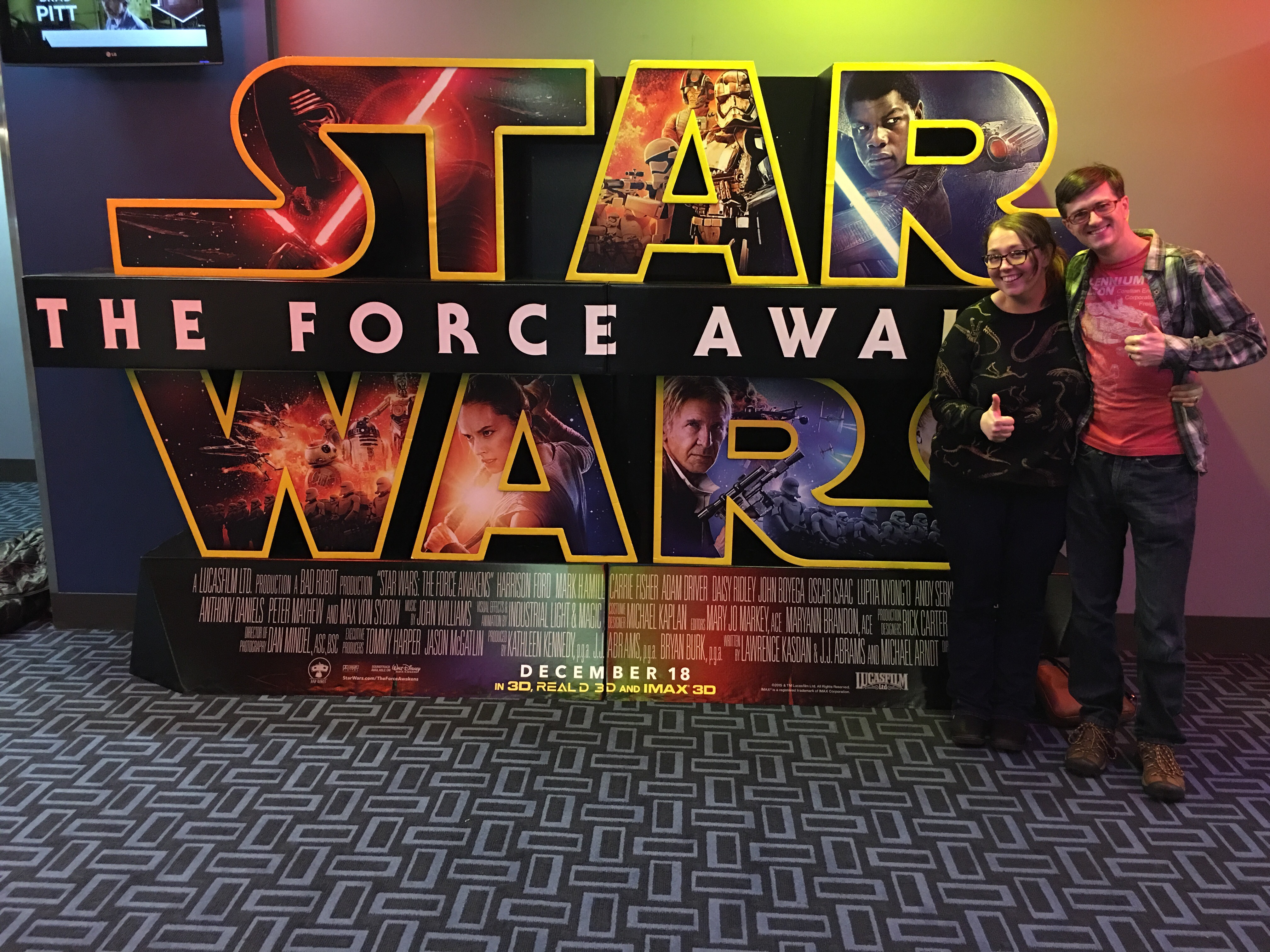 Andrle and Nick stand to the right of a large Star Wars: The Force Awakens poster