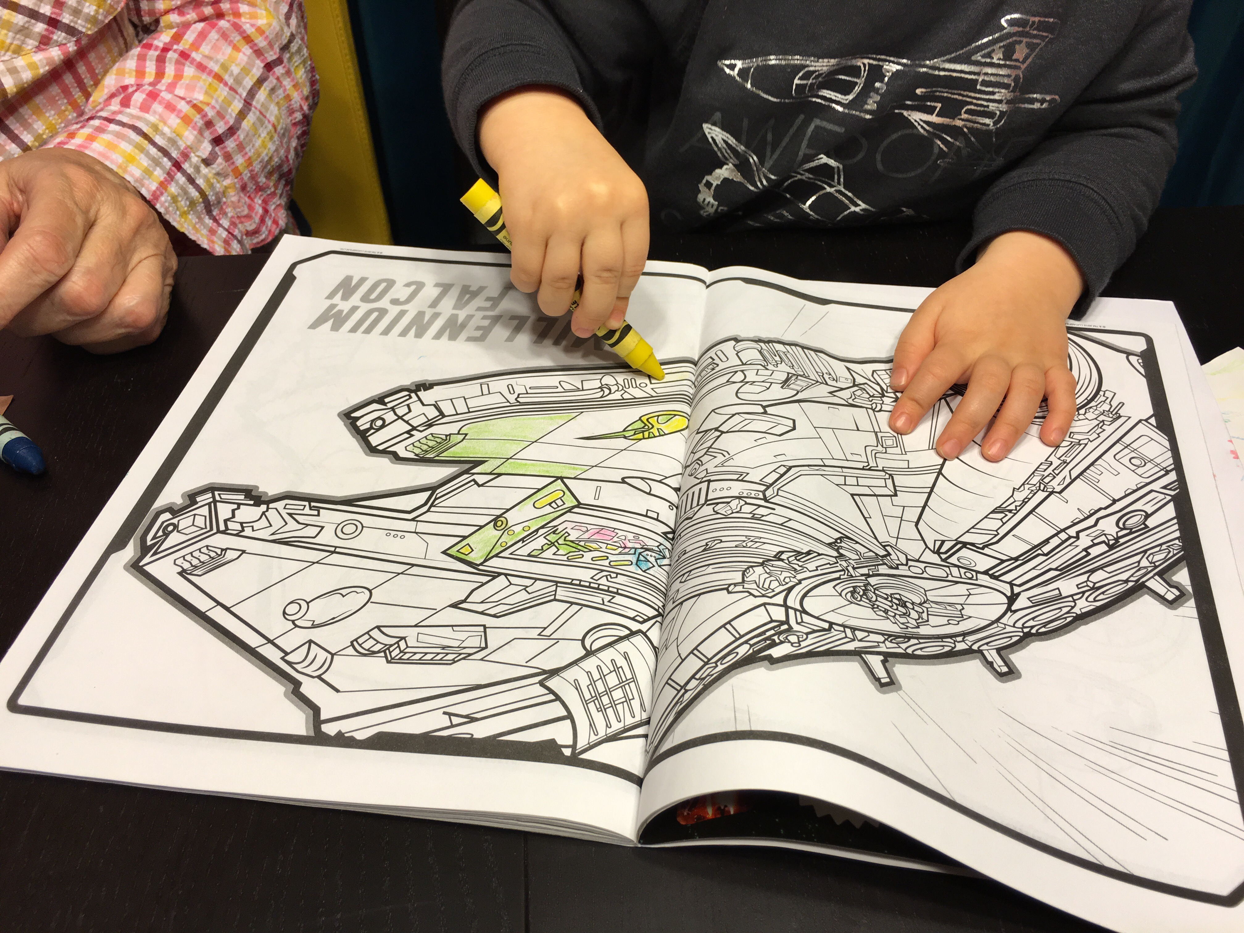 Toddler hands hold a big yellow crayon, carefully coloring a picture of the Millennium Falcon in a The Force Awakens coloring book