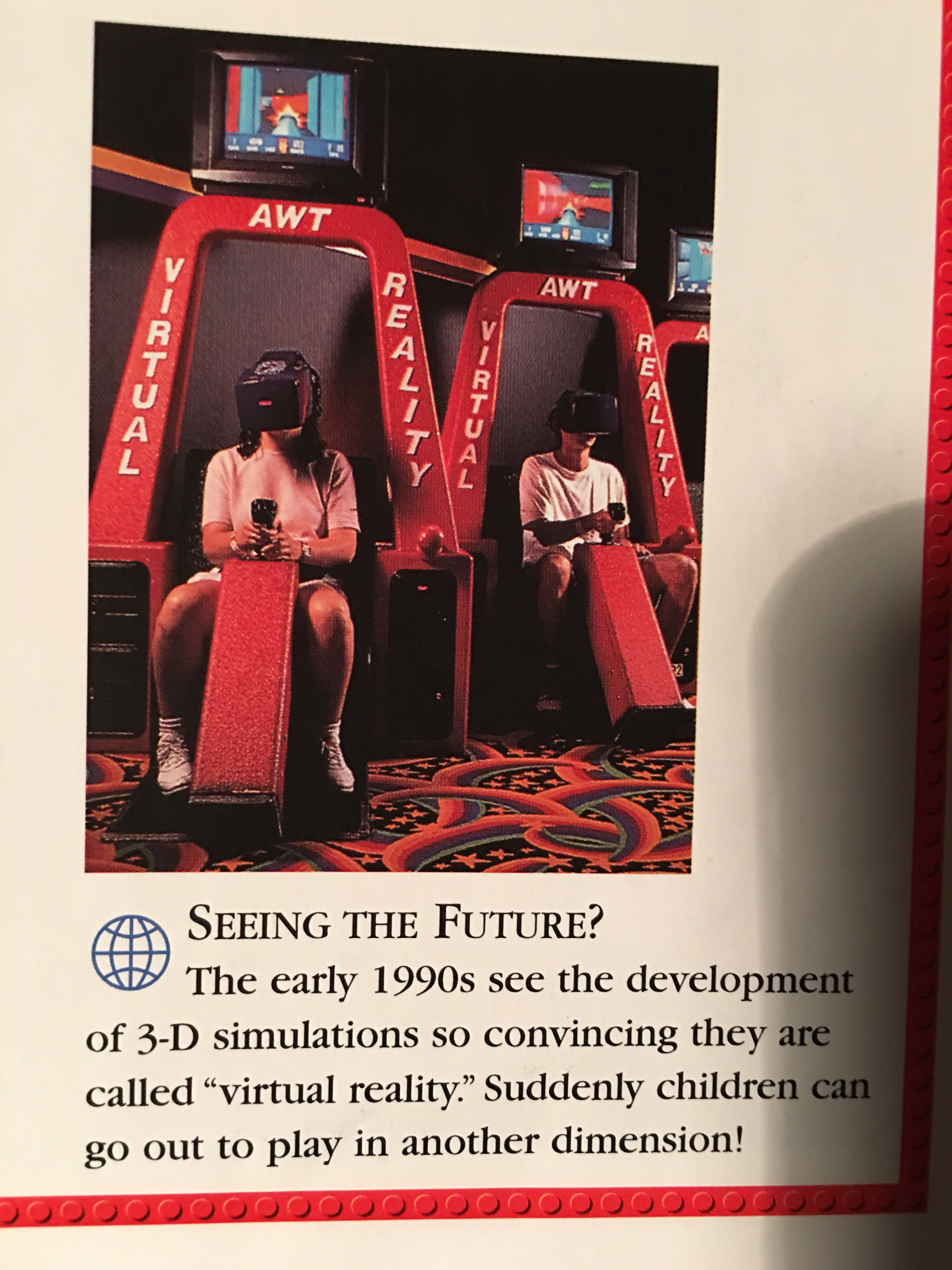 "A picture from a book about Lego shows two kids sitting in oversized arcade cabinets wearing huge VR goggles. The caption reads ""Seeing the future? The early 1990s see the development of 3-D simulations so convincing they are called 'virtual reality'. Suddenly children can go out to play in another dimension!"""