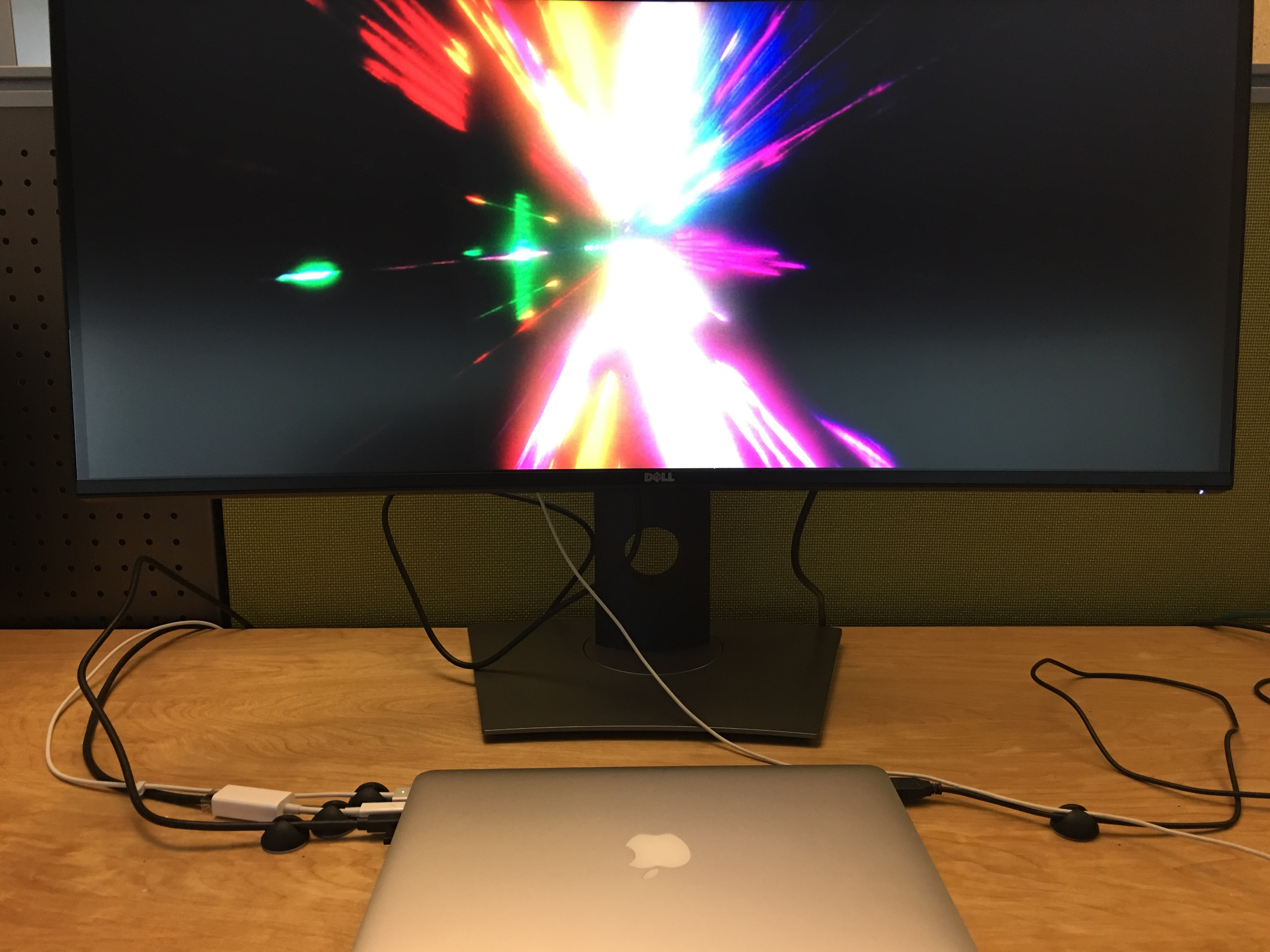 "A closed 13"" MacBookPro12,1 is connected to a widescreen monitor featuring an image of the rainbow colored stargate from the end of Kubrick's ""2001: A Space Odyssey"""