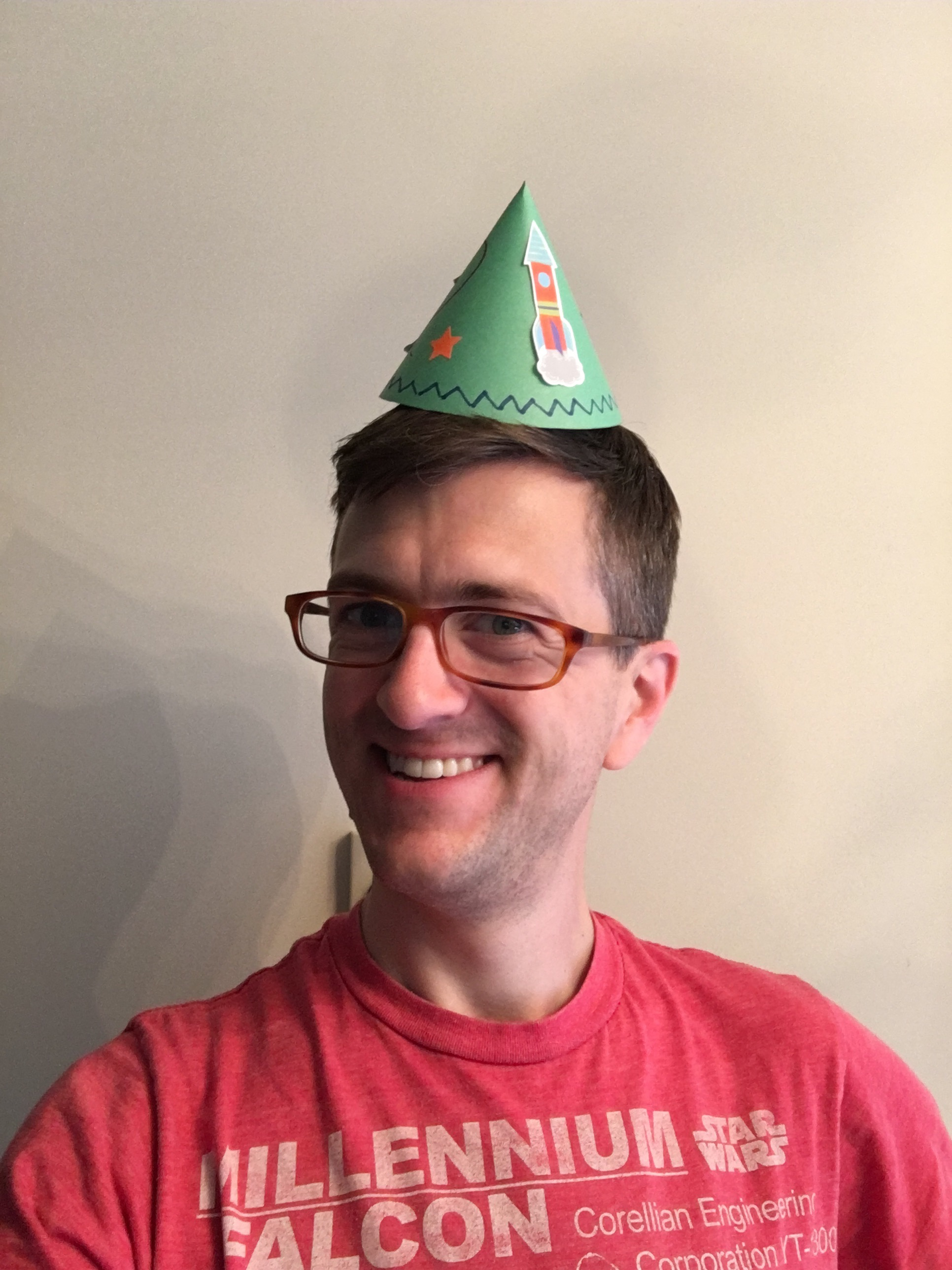 Selfie of Nick wearing a red Millennium Falcon shirt from Target and a green construction paper party hat with rocket stickers on it.