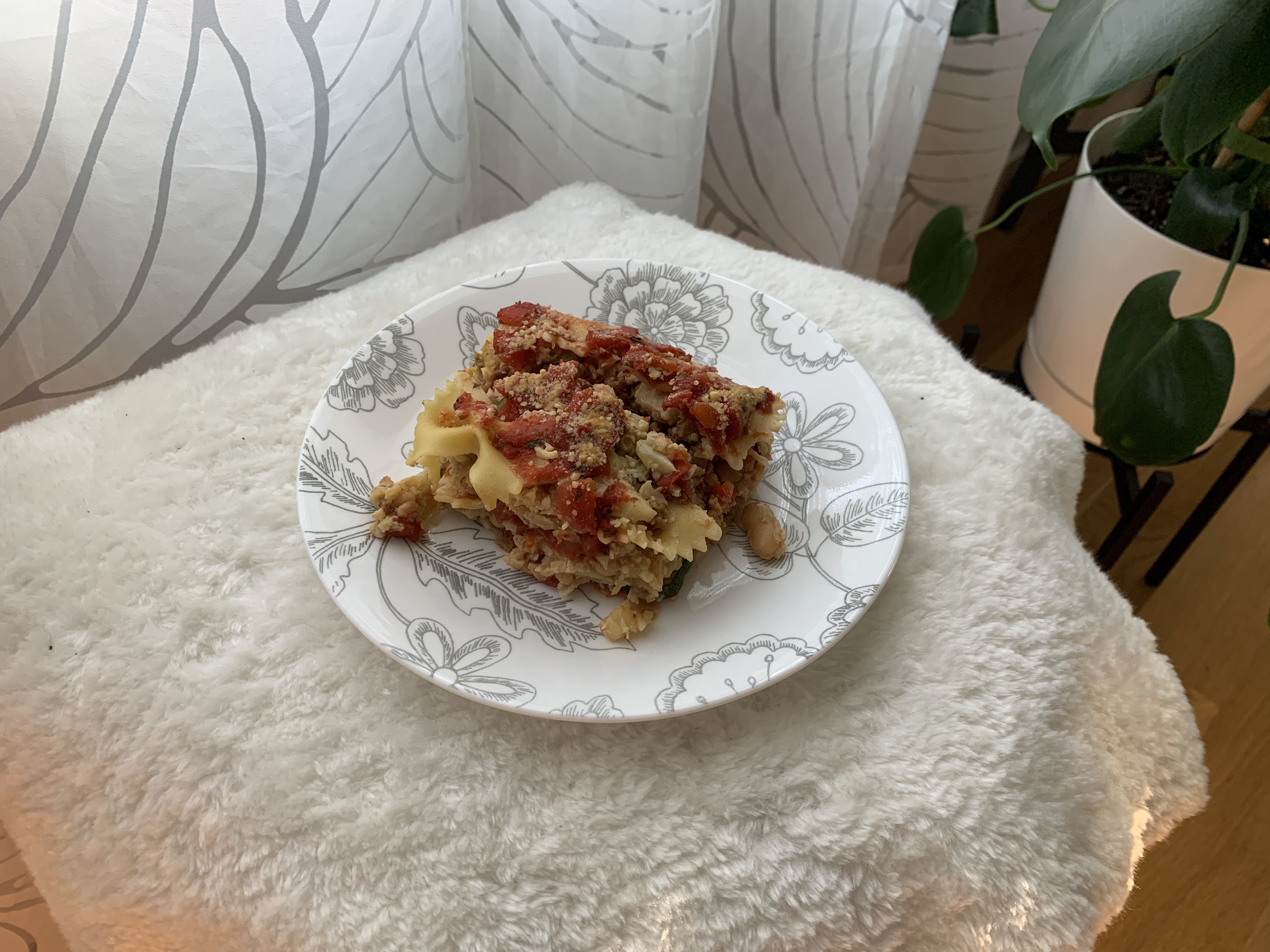 A serving of lasagna sits on a plate on a stool in front of a plant and some curtains