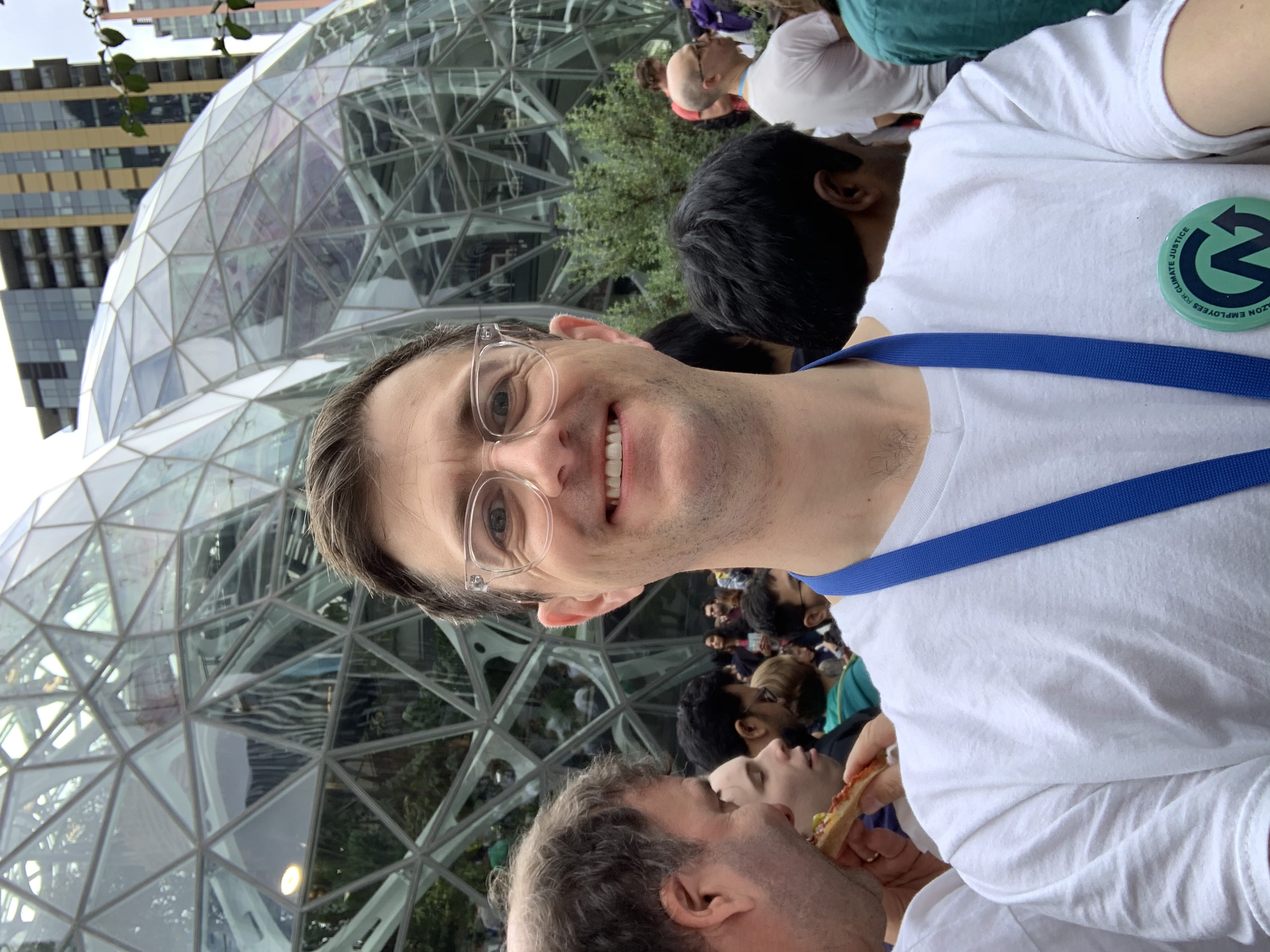 Selfie of Nick in front of The Spheres wearing a white shirt and Amazon Employees for Climate Justice button