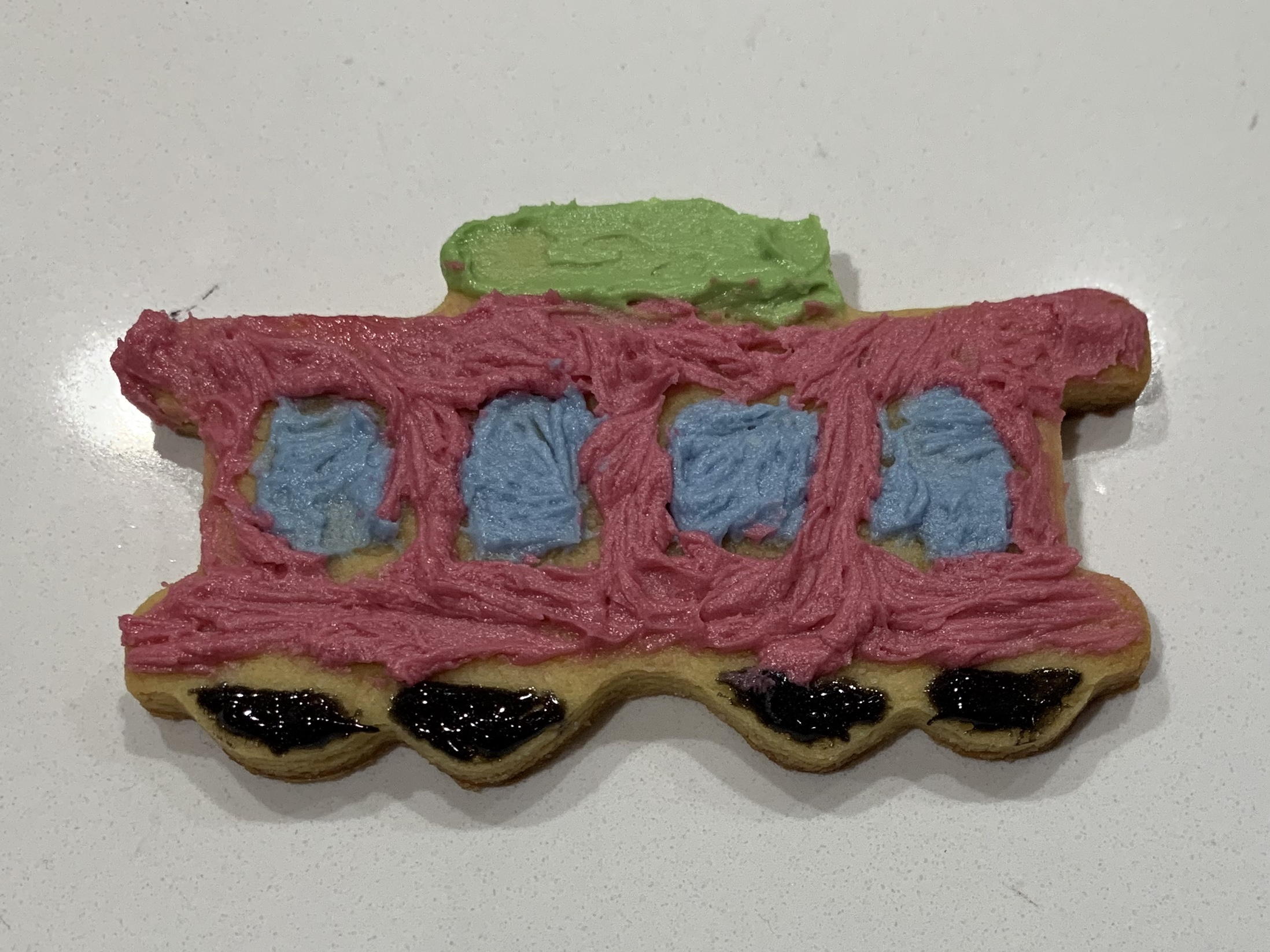 A trolley shaped sugar cookie, frosted in red with blue windows and black wheels