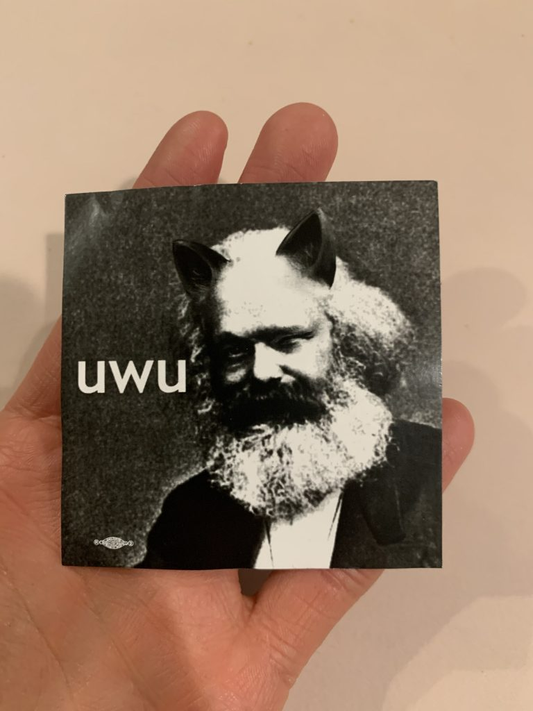 "Hand holding photoshopped sticker of Karl Marx with cat ears saying ""uwu"""
