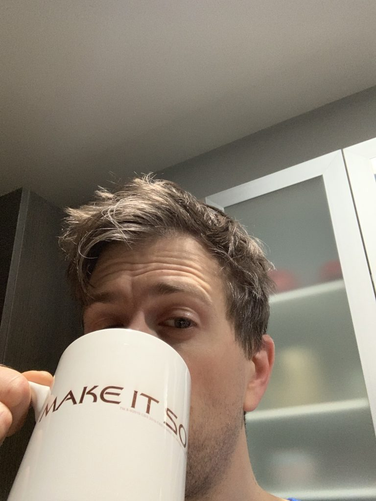 Sleepy bed head Nick drinking coffee from a Make It So mug