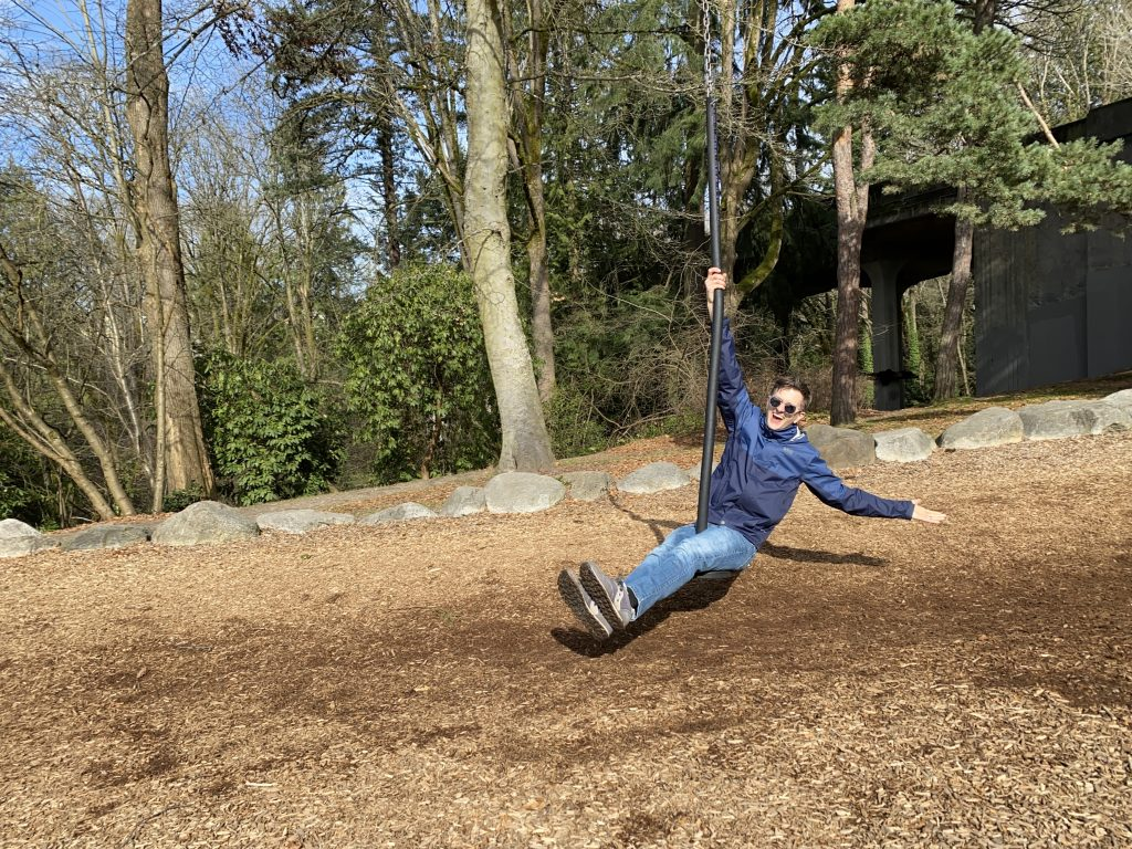 Nick dangling from a zip line with arm outstretched  on a sunny day in a park