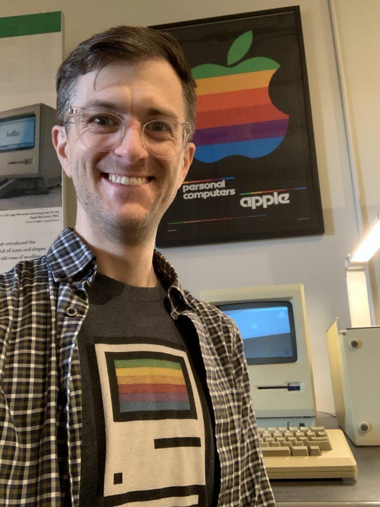 Nick wearing a Mac classic shirt in front of a Mac Classic