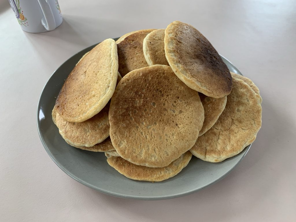 A large pile of golden brown pancakes on a grey plate in the middle of a table