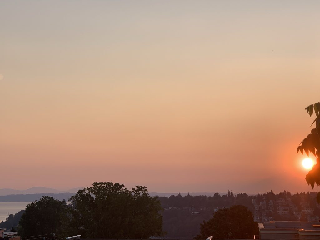 A reddish sun sets over sound and mountains through wildfire smoke